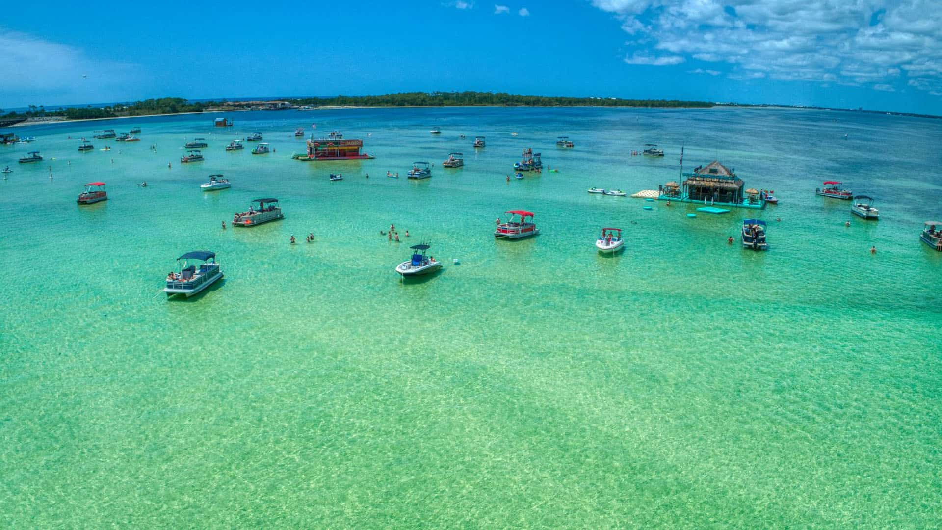 Dozens of boats parked in crystal clear blue water on sunny day